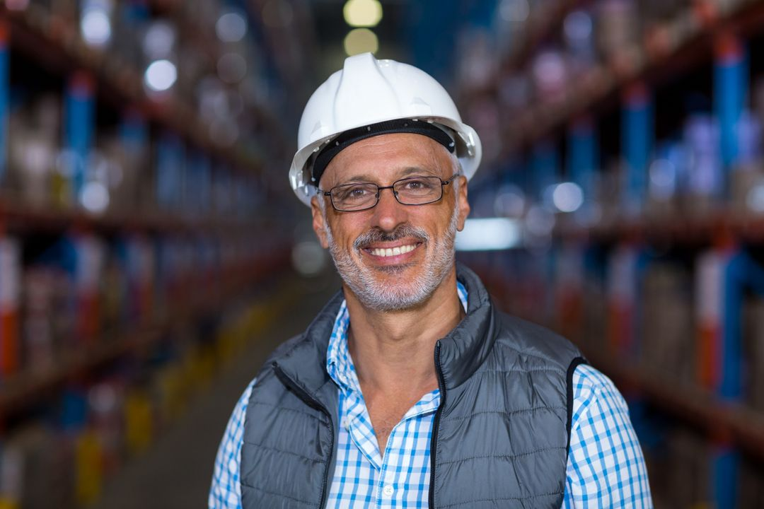 Portrait of happy worker is posing with hard hat in a warehouse Free Stock Images from PikWizard