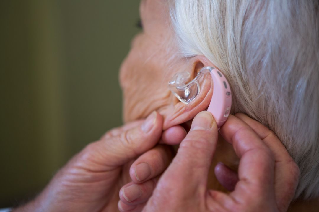Doctor inserting hearing aid in senior patient ear in hospital Free Stock Images from PikWizard