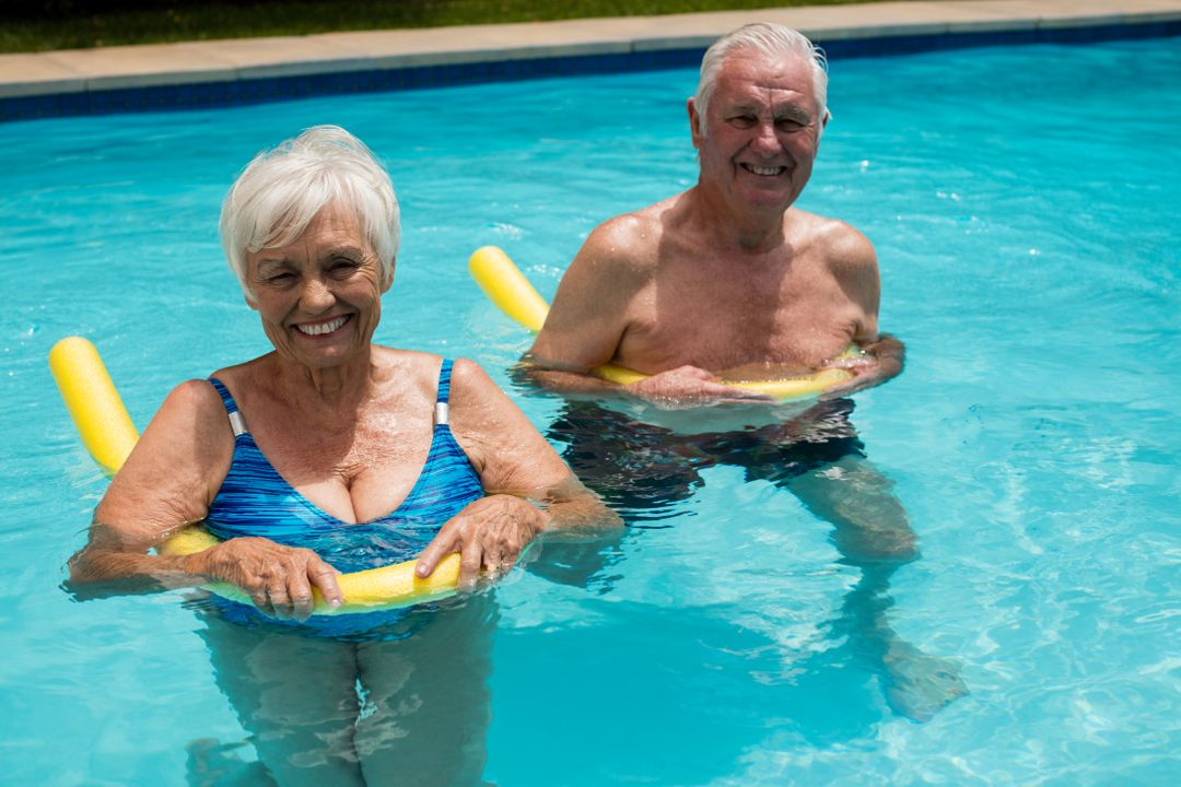 Happy senior couple swimming in the pool with inflatable tubes