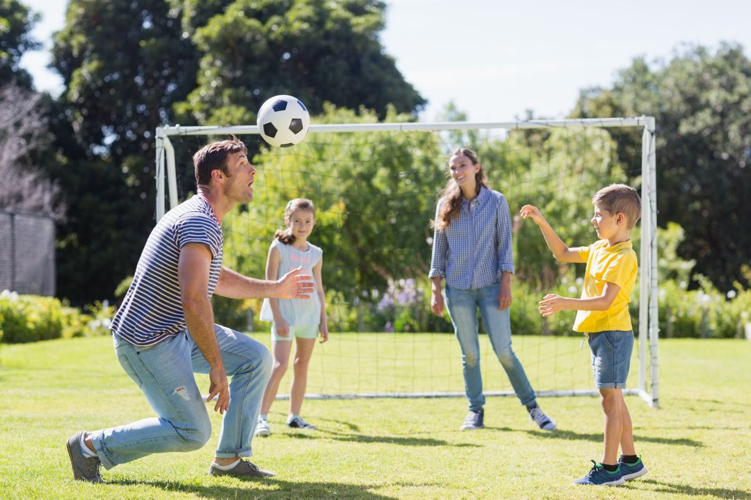 Happy family playing football in the park on a sunny day