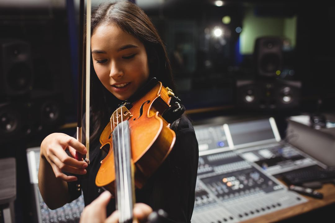Female student playing violin in a studio Free Stock Images from PikWizard
