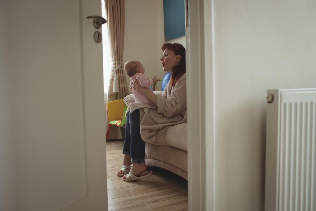 Side view of mother with baby sitting on bed seen through open door