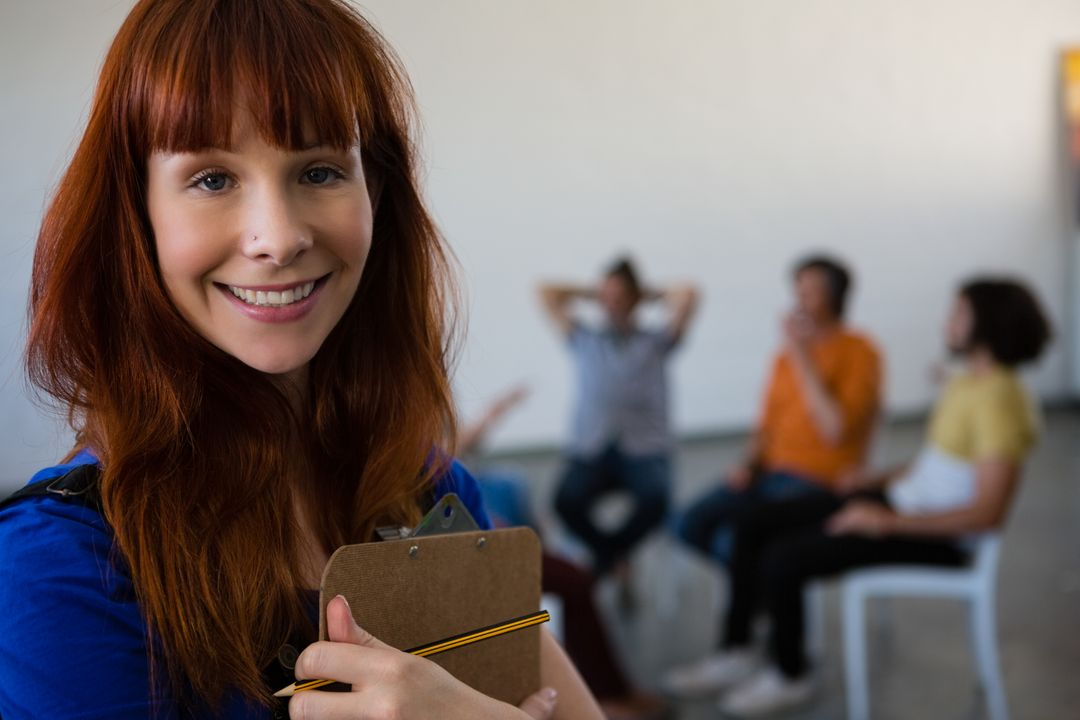 Portrait of female teacher holding clipboard with students talking in background at art class Free Stock Images from PikWizard