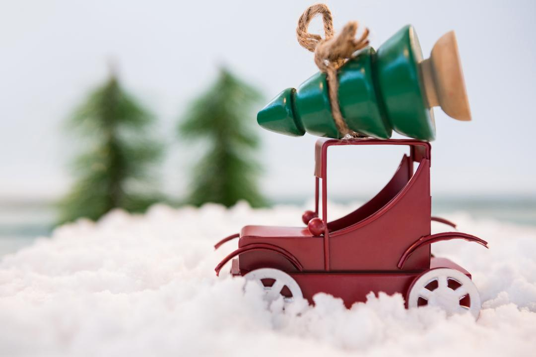 Toy car carrying christmas tree on fake snow