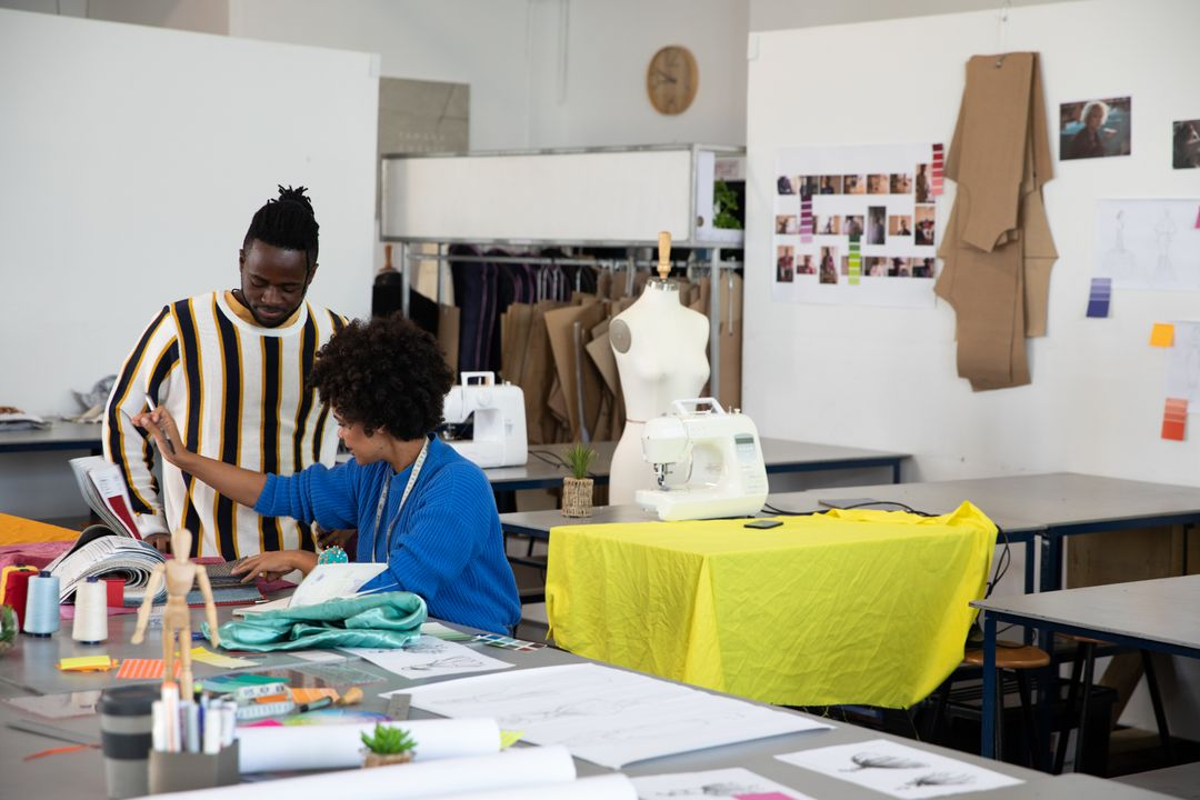 Side view of a young African American male fashion student and a young mixed race female fashion student discussing a design together at a worktable in a studio at fashion college, with mannequins in the background.
