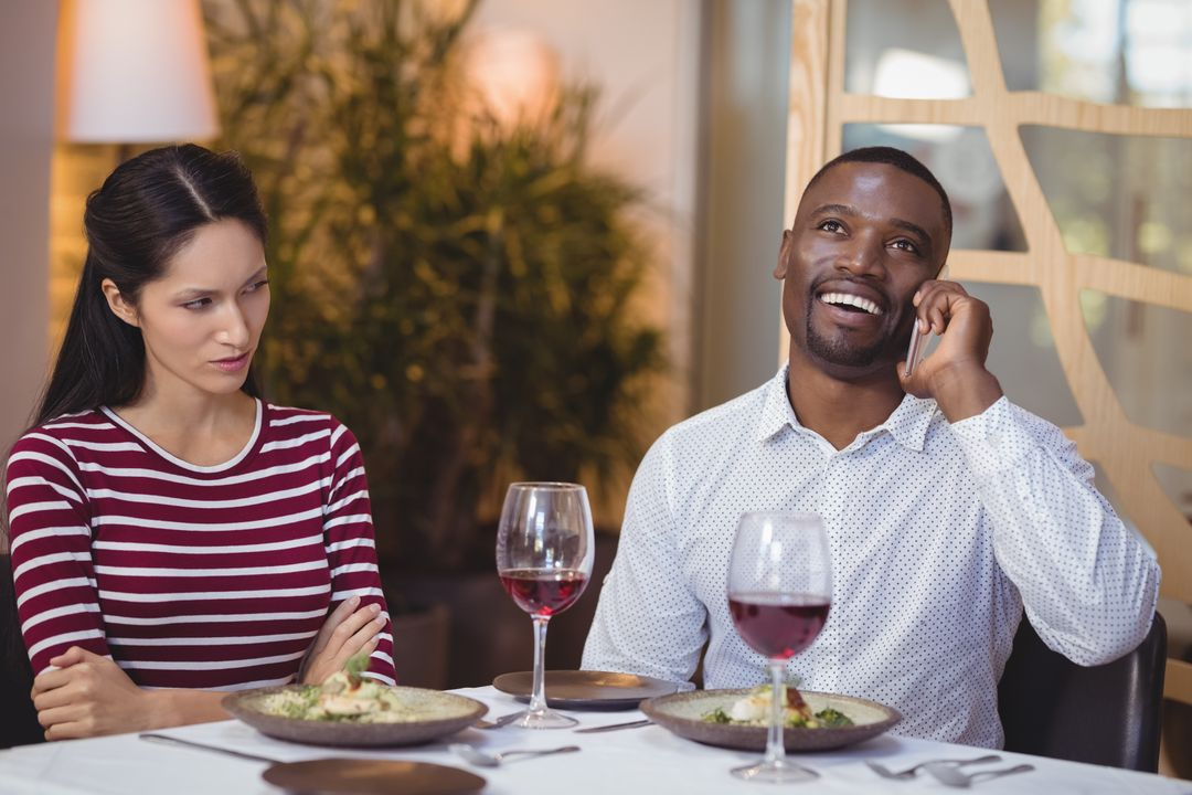 Man ignoring bored woman while talking on mobile phone in restaurant