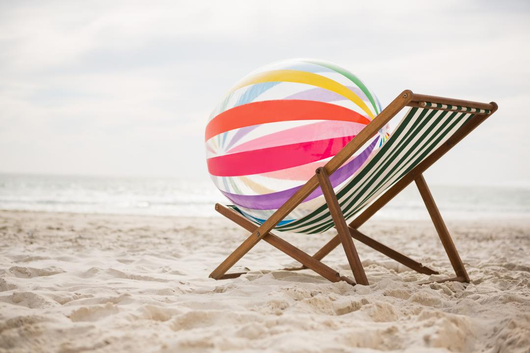 Striped beach ball kept on empty beach chair at tropical sand beach Free Stock Images from PikWizard