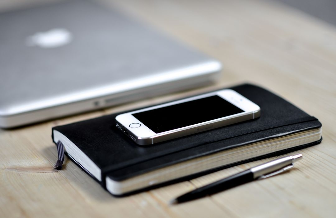 Macbook, iPhone, notebook and a pen placed on a wooden desk