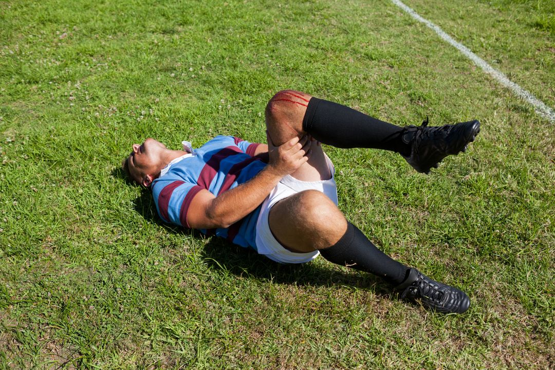 Full length of rugby player with injured knee lying on field during sunny day Free Stock Images from PikWizard