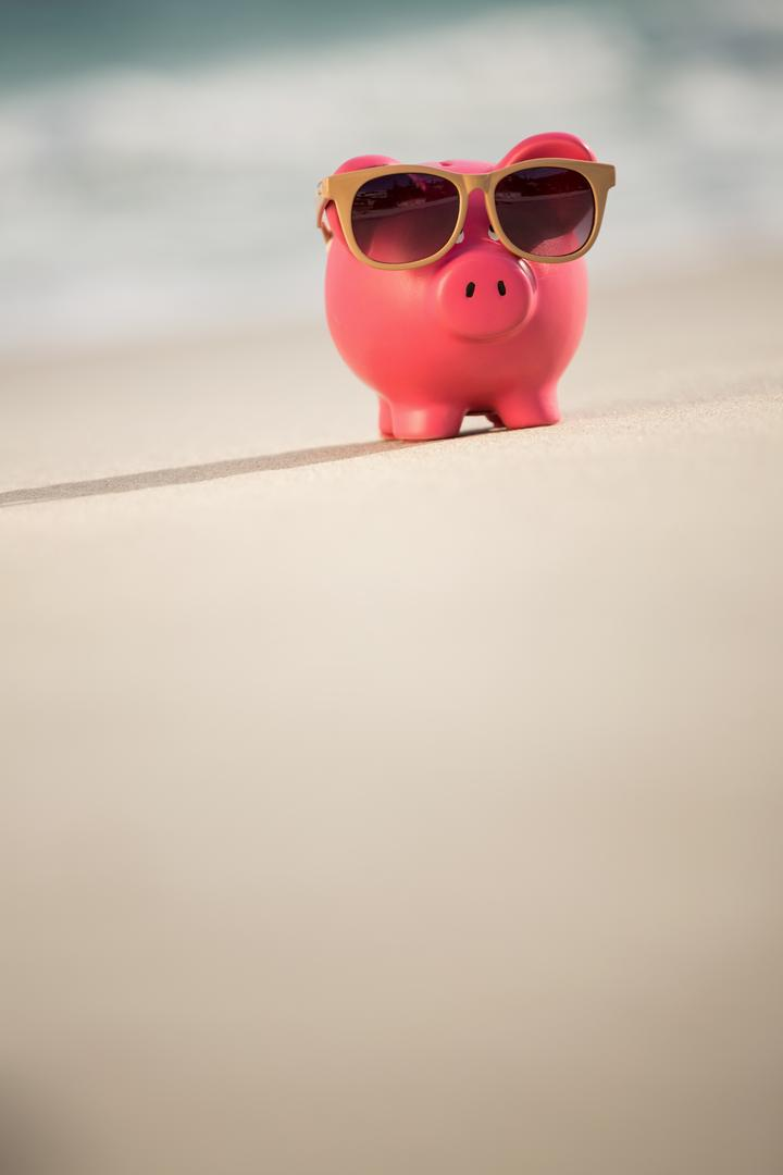 Summer piggy bank with sunglasses on sand at beach