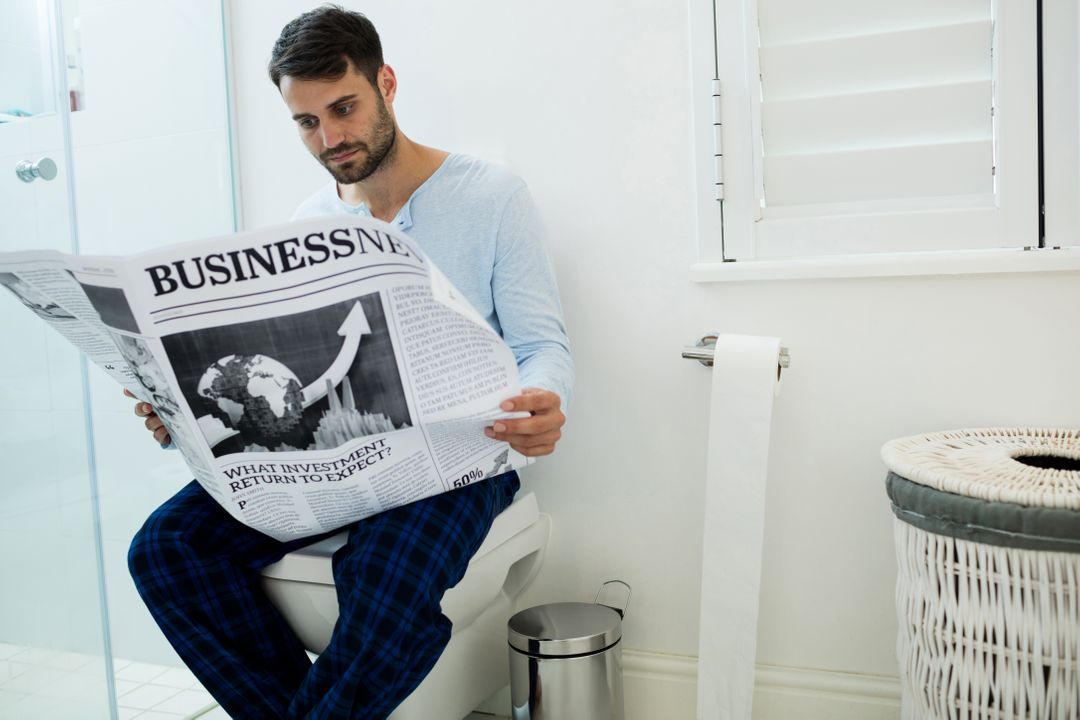 Man sitting on toilet seat reading a newspaper at home