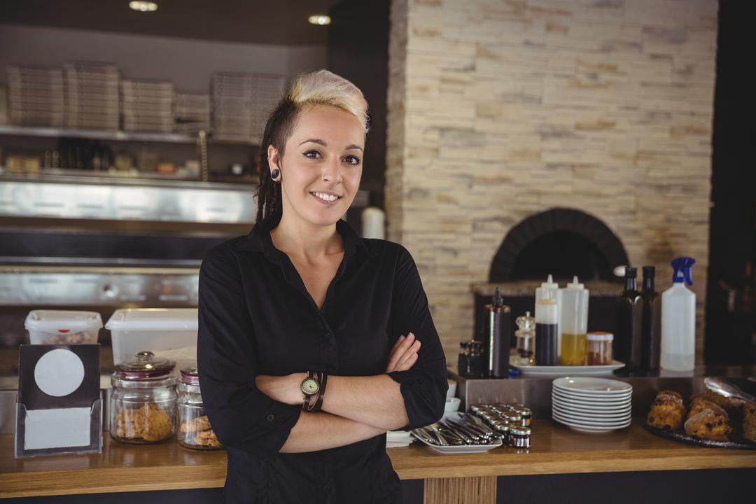 Woman standing with arms crossed in kitchen at café