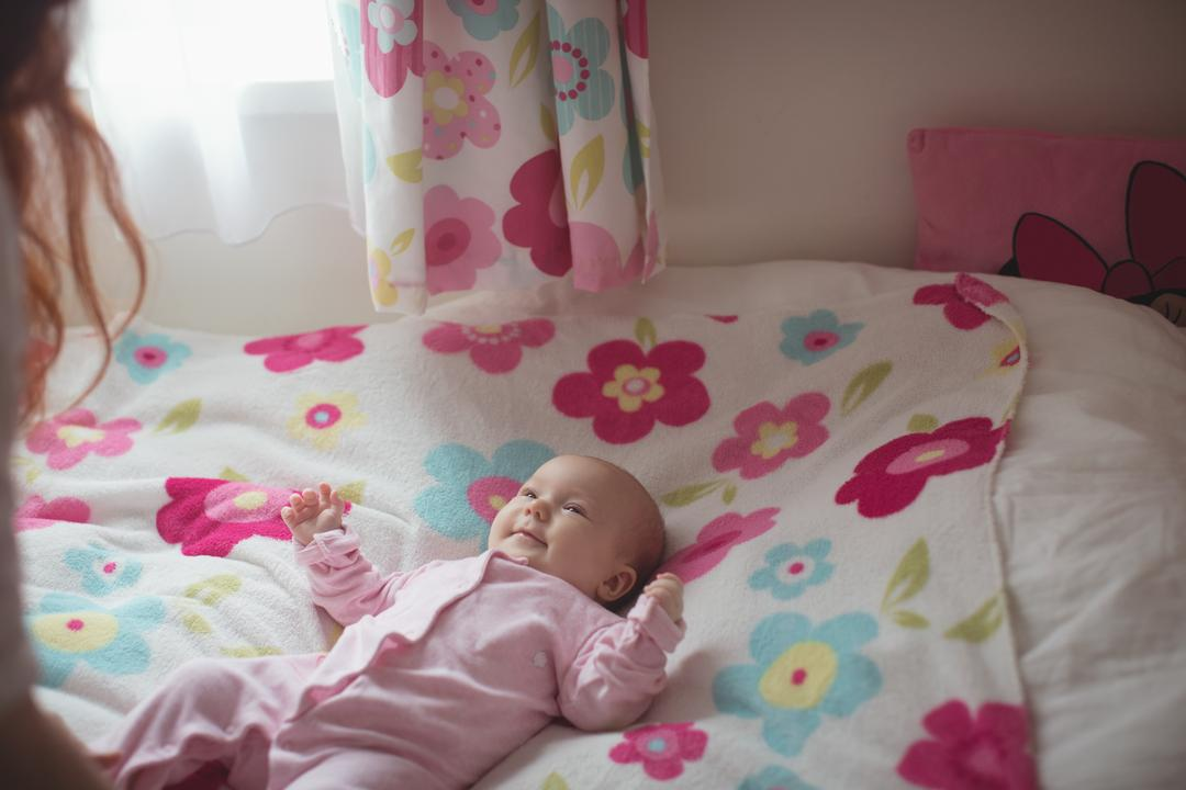 Cute baby looking at mother while lying in bed