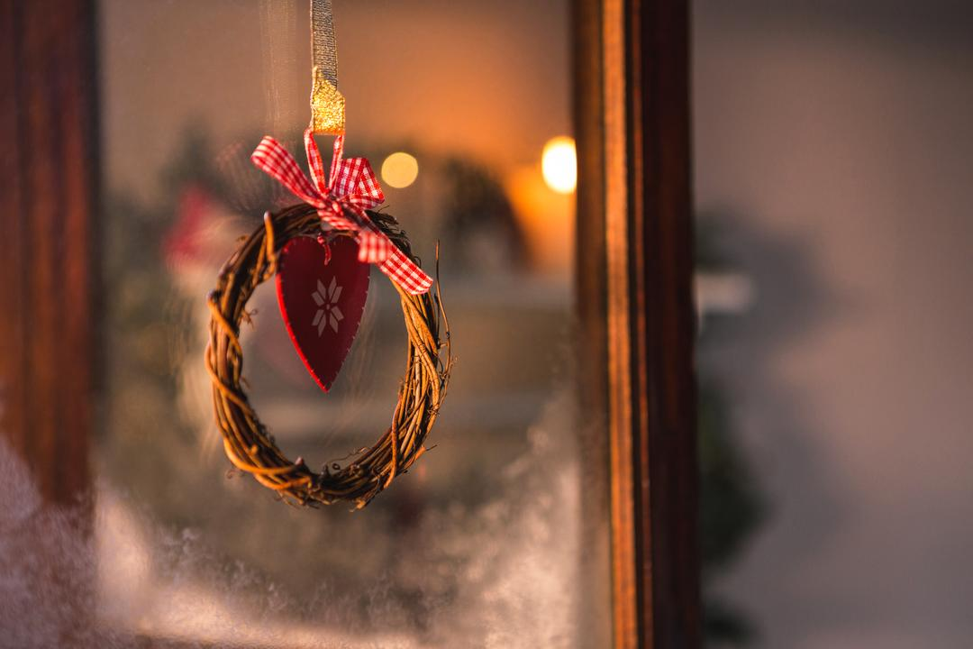 Close-up of christmas grapevine wreath with ribbon hanging on window