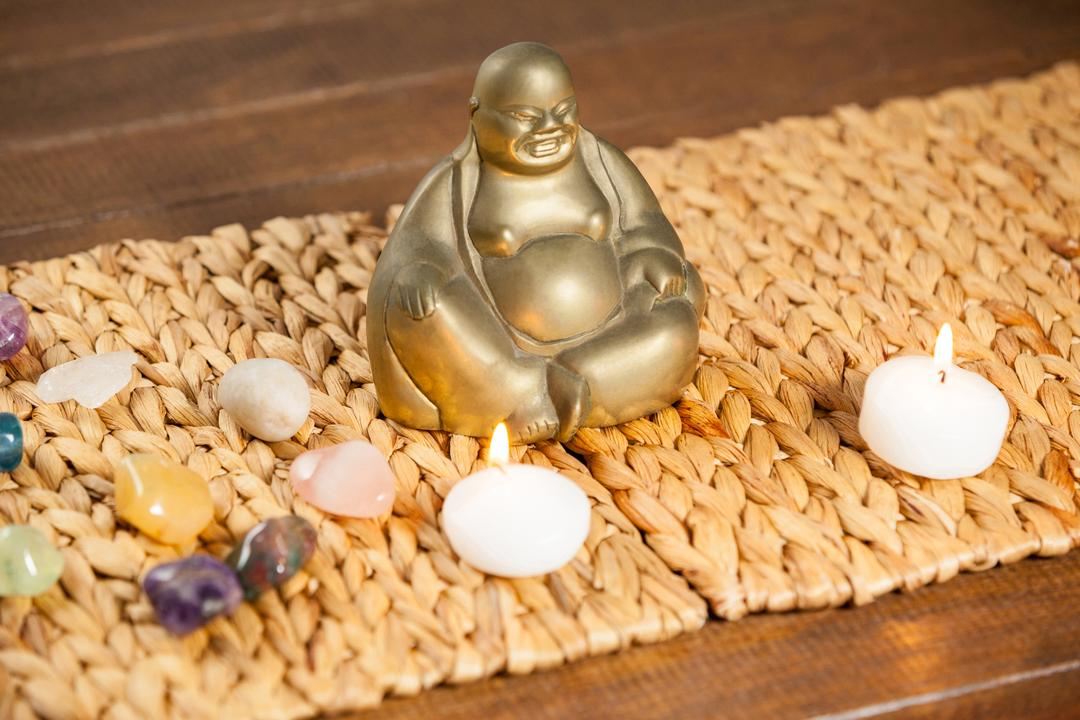 Laughing buddha figurine, pebbles stone and lit candles on mat
