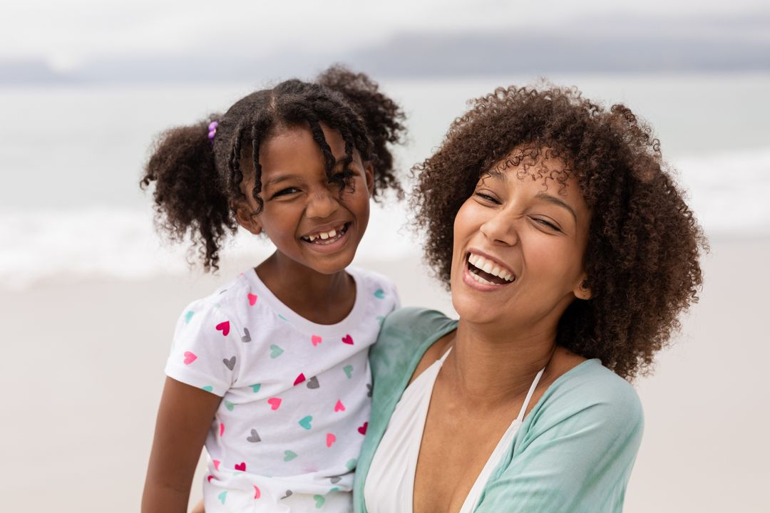 Portrait of happy African American Mother and daughter standing together at beach on a sunny day