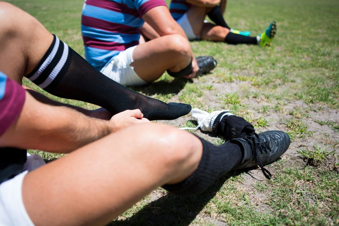 High angle view of rugby players wearing socks while sitting on field Free Stock Images from PikWizard