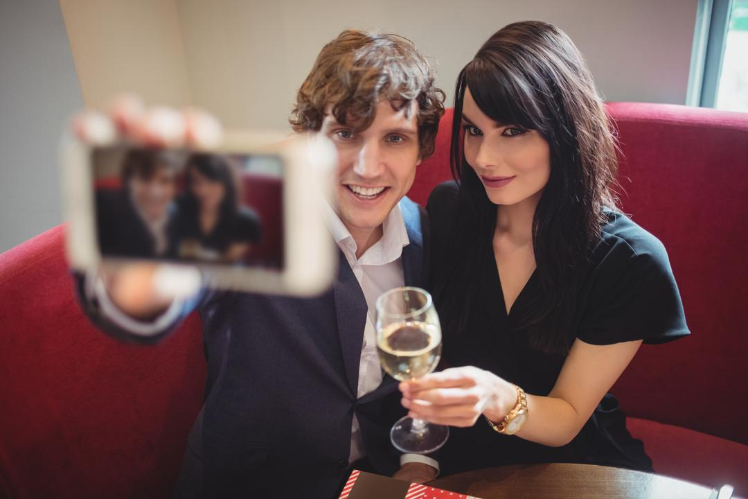 Couple holding drink and taking a selfie in restaurant