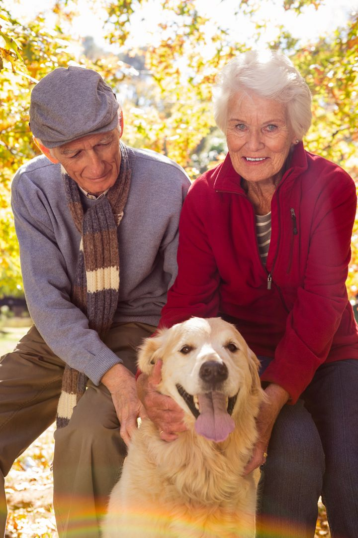 Portrait of elderly couple with their pet dog in the park