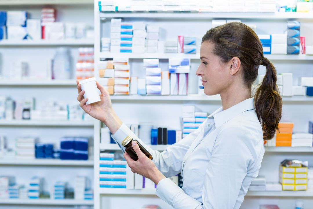 Pharmacist checking a bottle of drug in pharmacy