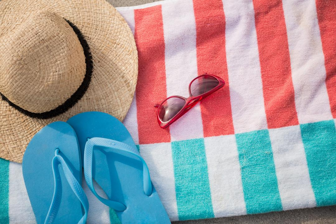 Straw hat, blue flip flop and sunglasses kept on beach blanket at tropical beach