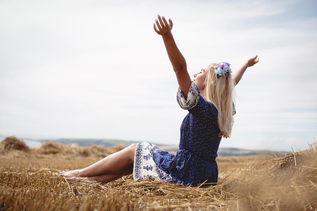 Carefree blonde woman sitting in field with her arms raised