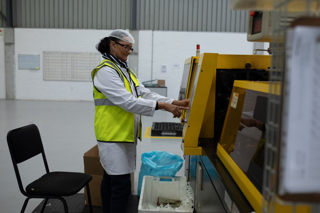 Side view of focused Caucasian female worker working in a factory warehouse, wearing hair net, glasses, lab coat and a high visibility vest, operating a machine on the production line Free Stock Images from PikWizard