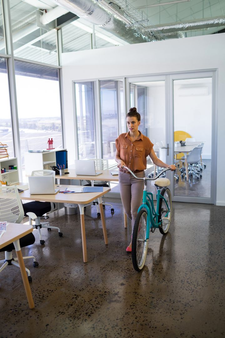 Female executive walking with bicycle in the office Free Stock Images from PikWizard