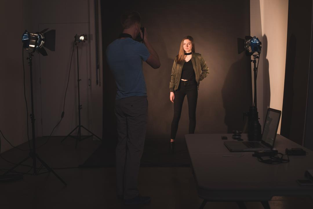 Behind the scenes image of a photoshoot, woman posing being photographed