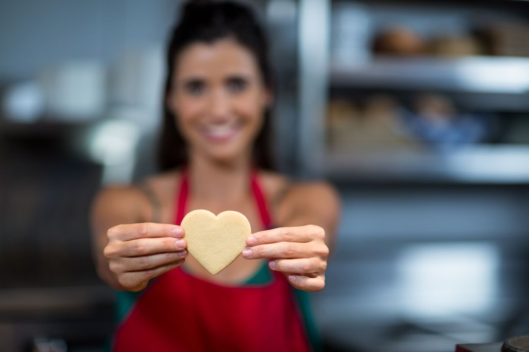 Close-up of female staff showing heart shape cookie at counter in bake shop
