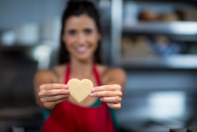 Close-up of female staff showing heart shape cookie at counter