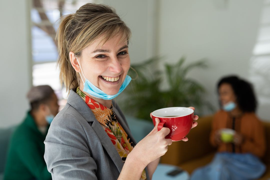 A caucasian woman at the office with her facemask pulled down holding a cup of coffee smiling. Behind her are her colleagues sitting on the couch talking during their coffee break. Free Stock Images from PikWizard