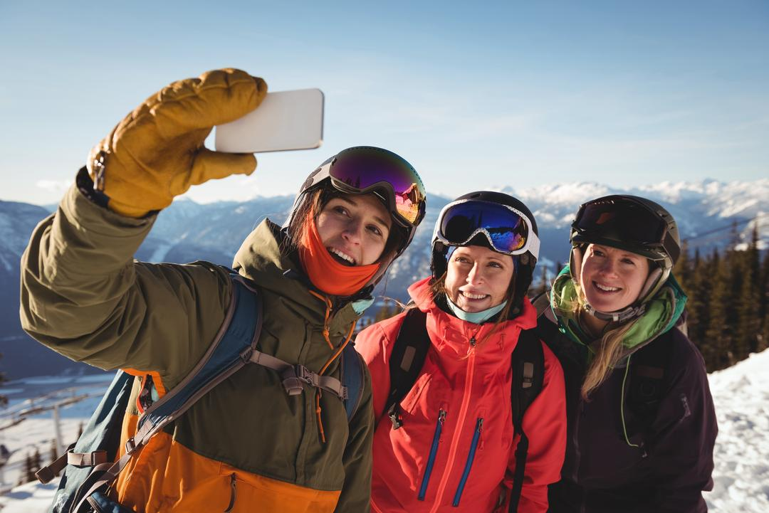 Three smiling female skiers taking selfie on mobile phone during winter