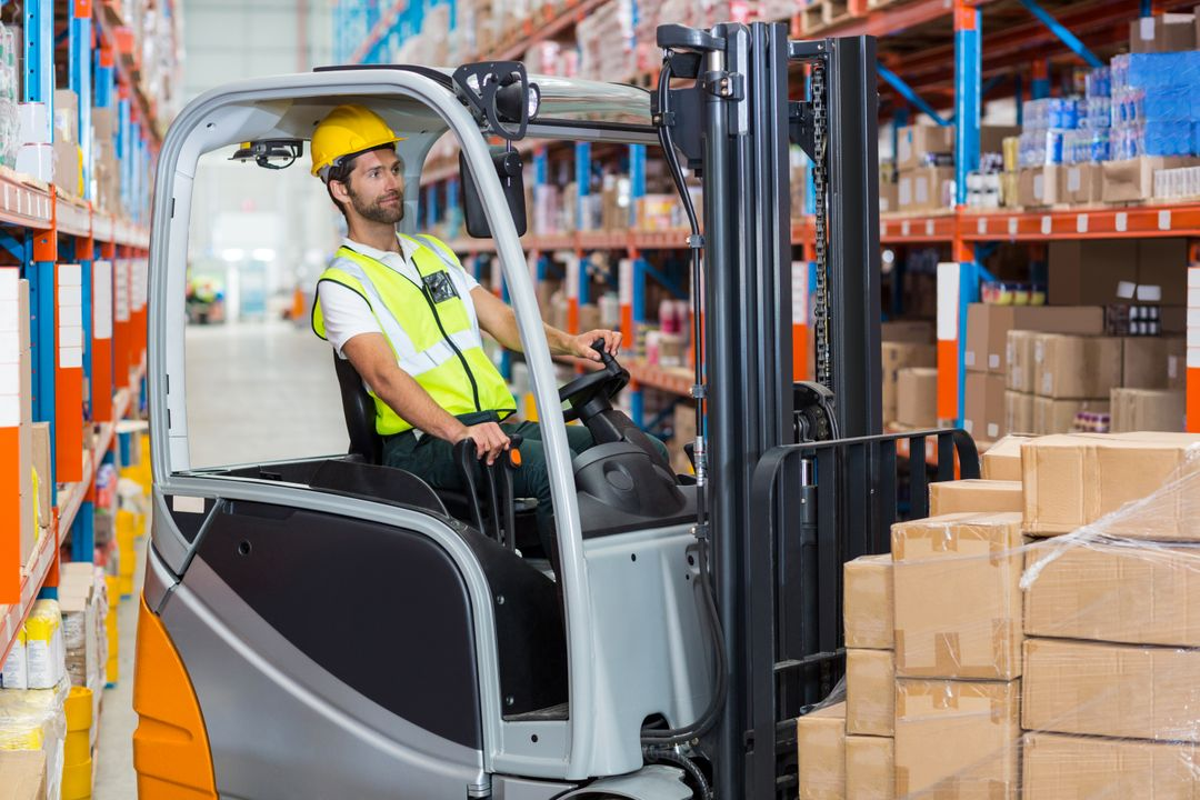 Male worker using forklift in warehouse Free Stock Images from PikWizard