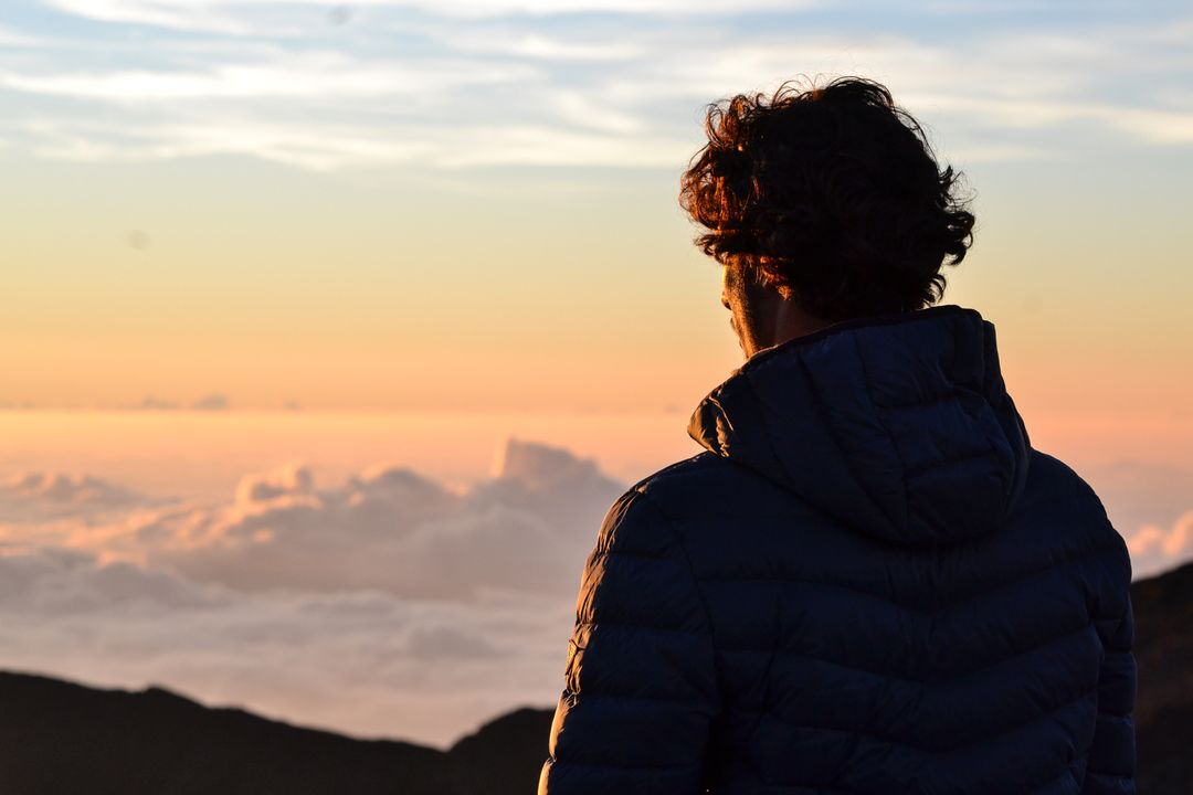 Man looking out from mountain top at sunrise