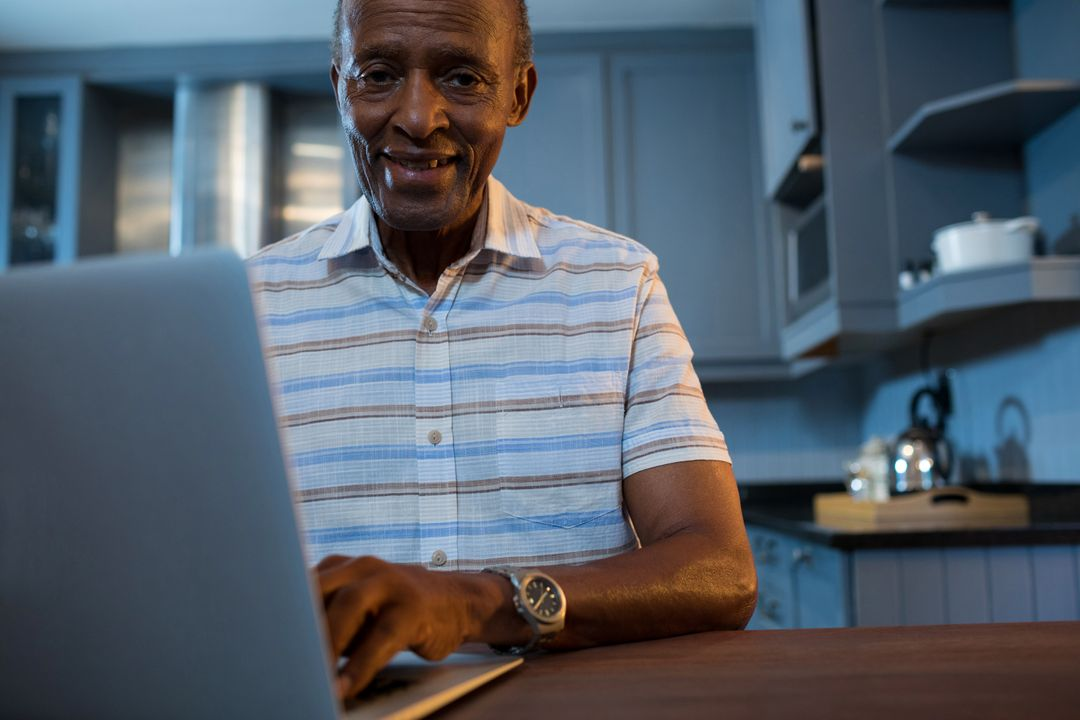 Portrait of senior man using laptop while sitting home Free Stock Images from PikWizard