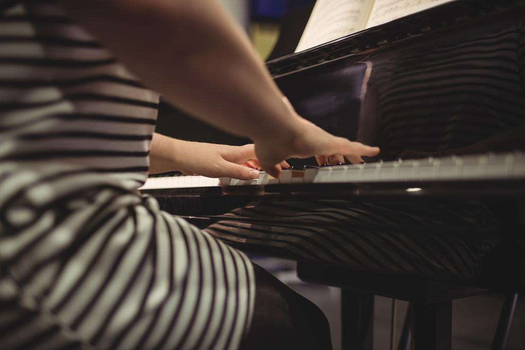 Mid-section of female student playing piano in a studio Free Stock Images from PikWizard
