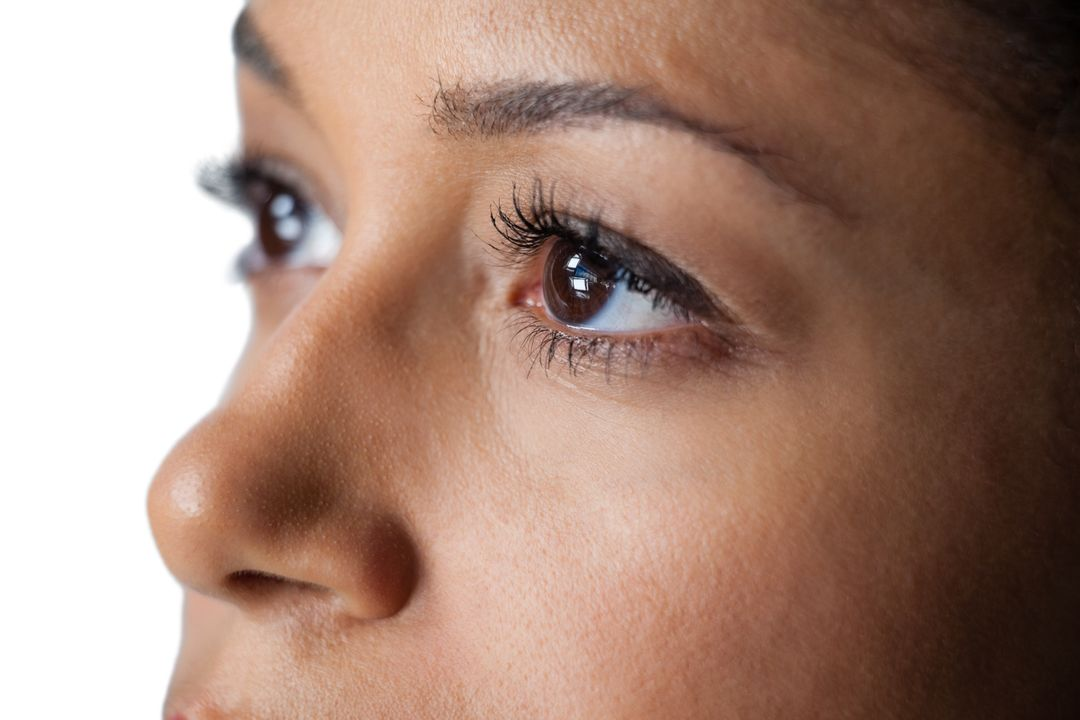 Close-up of womans eye and nose against white background