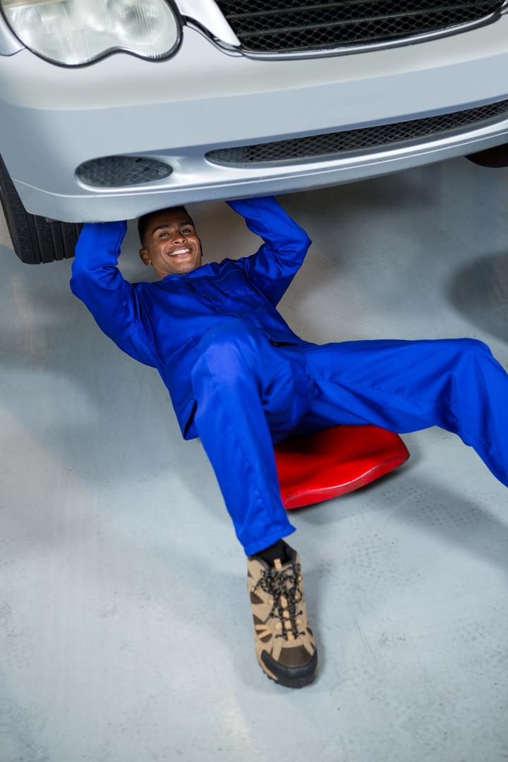 Portrait of happy mechanic repairing a car at repair garage