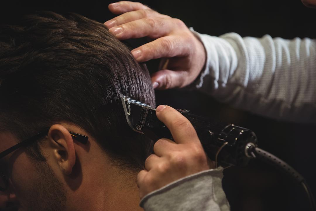 Close-up of man getting his hair trimmed with trimmer in barber shop