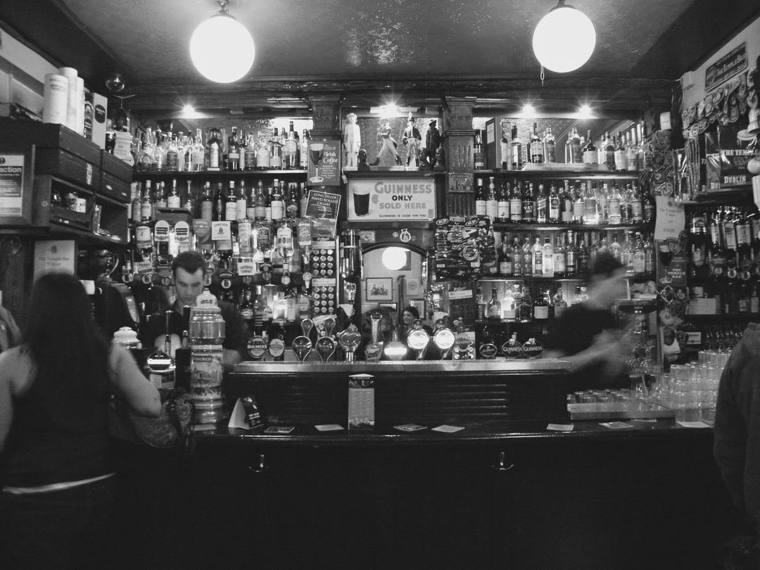 black and white image of a bar scene with workers zoom background