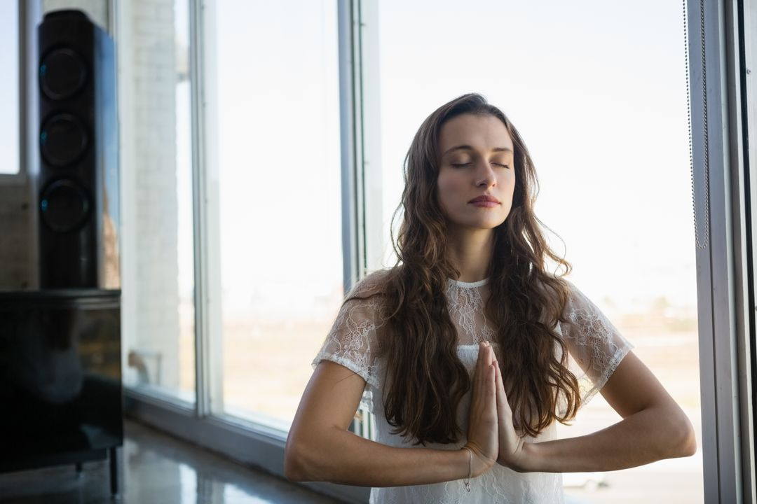 Young woman with eyes closed doing yoga at office