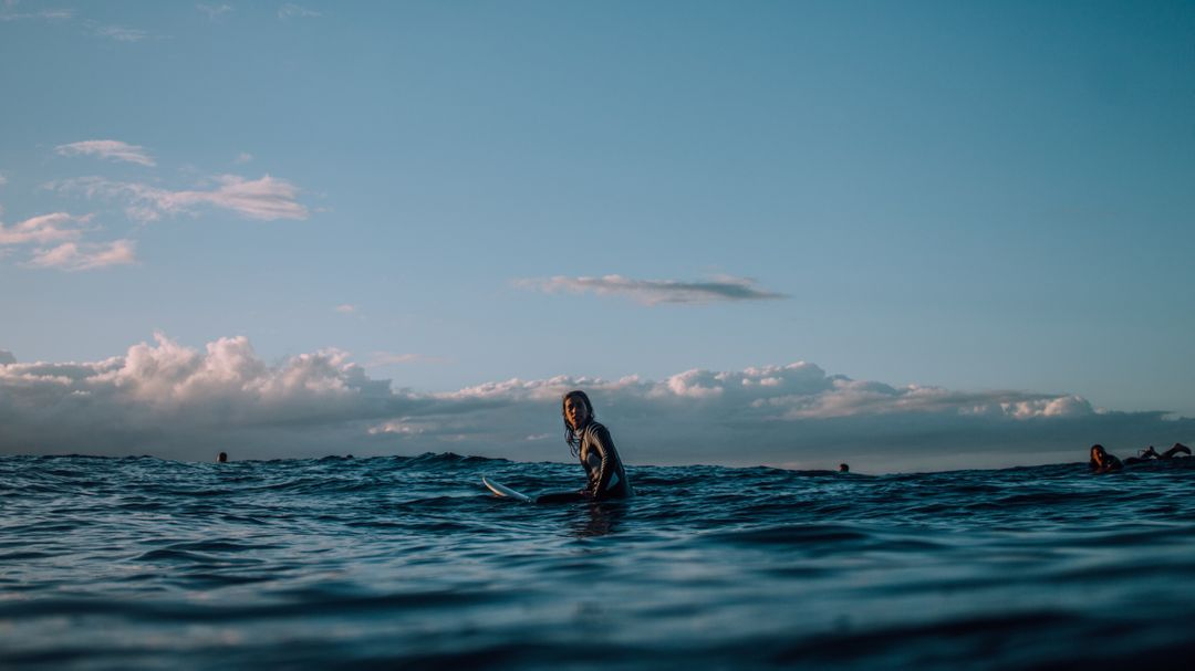 Photograph of woman sitting on surf board in the ocean