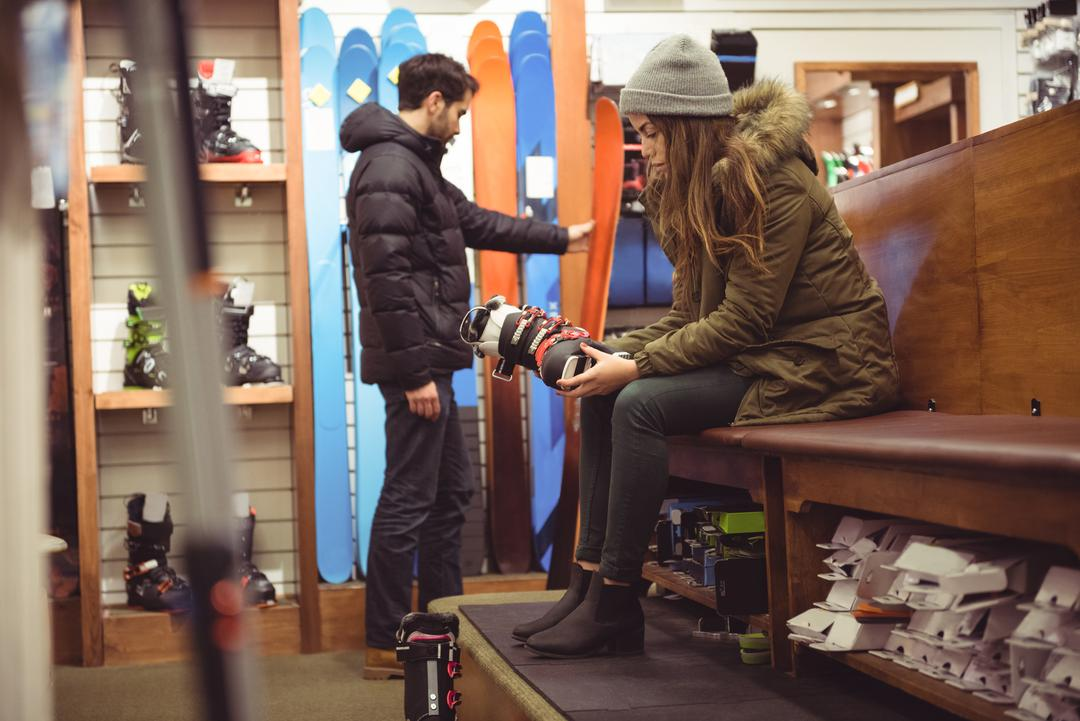 Woman trying on ski boot while man selecting ski in a shop