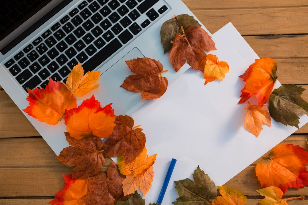 Overhead view of autumn leaves with paper by laptop on wooden table Free Stock Images from PikWizard