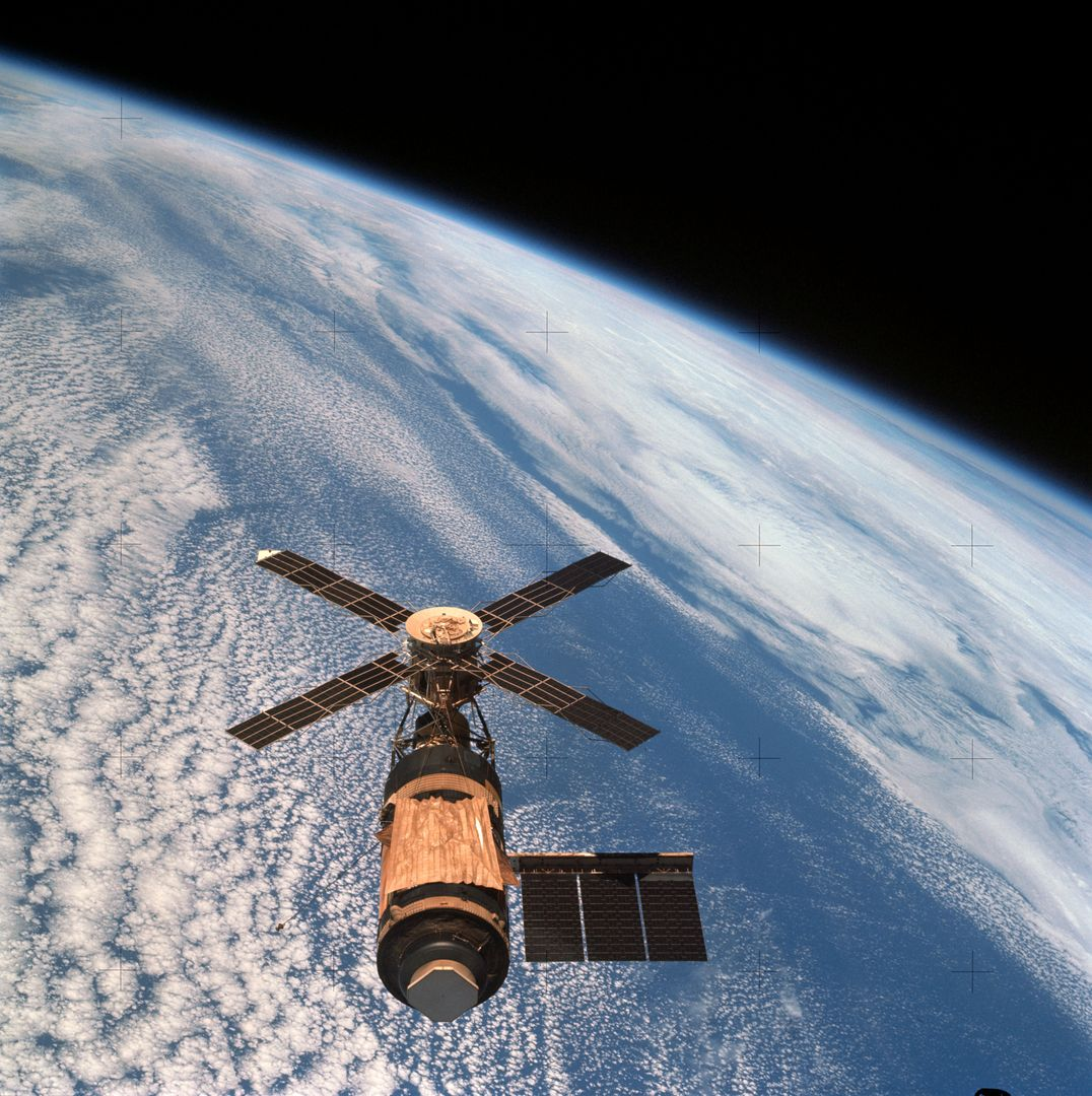 SL4-143-4706 (8 Feb. 1974) --- An overhead view of the Skylab space station cluster in Earth orbit as photographed from the Skylab 4 Command and Service Modules (CSM) during the final fly-around by the CSM before returning home. The space station is contrasted against a cloud-covered Earth. Note the solar shield which was deployed by the second crew of Skylab and from which a micro meteoroid shield has been missing since the cluster was launched on May 14, 1973. The Orbital Workshop (OWS) solar panel on the left side was also lost on workshop launch day. Inside the Command Module (CM) when this picture was made were astronaut Gerald P. Carr, commander; scientist-astronaut Edward G. Gibson, science pilot; and astronaut William R. Pogue, pilot.  The crew used a 70mm hand-held Hasselblad camera to take this photograph. Photo credit: NASA