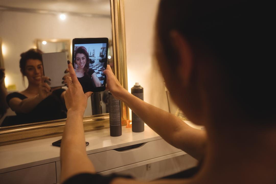 Woman taking selfie from mobile phone at saloon Free Stock Images from PikWizard