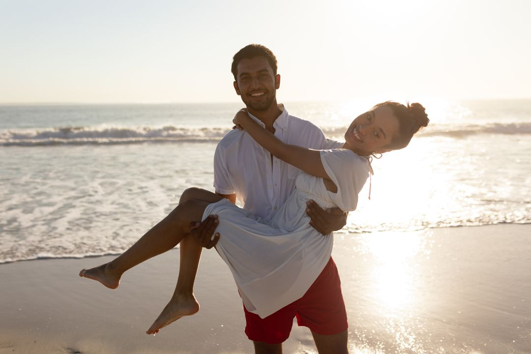 Portrait of man carrying woman in his arms on the beach