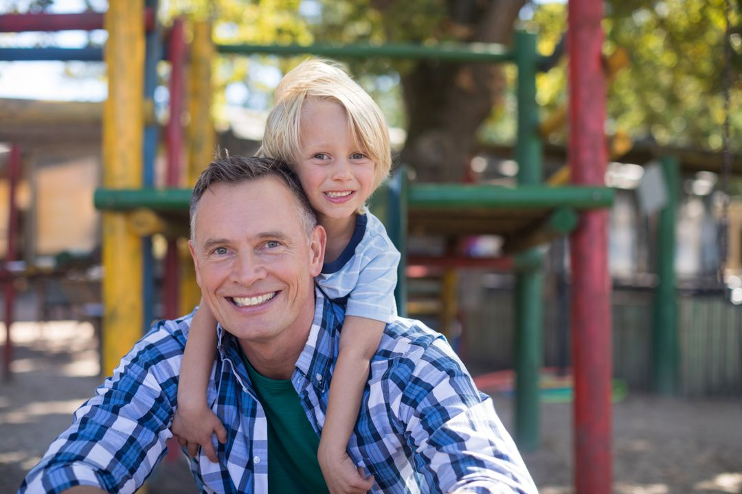 Portrait of happy son leaning on father at playground Free Stock Images from PikWizard