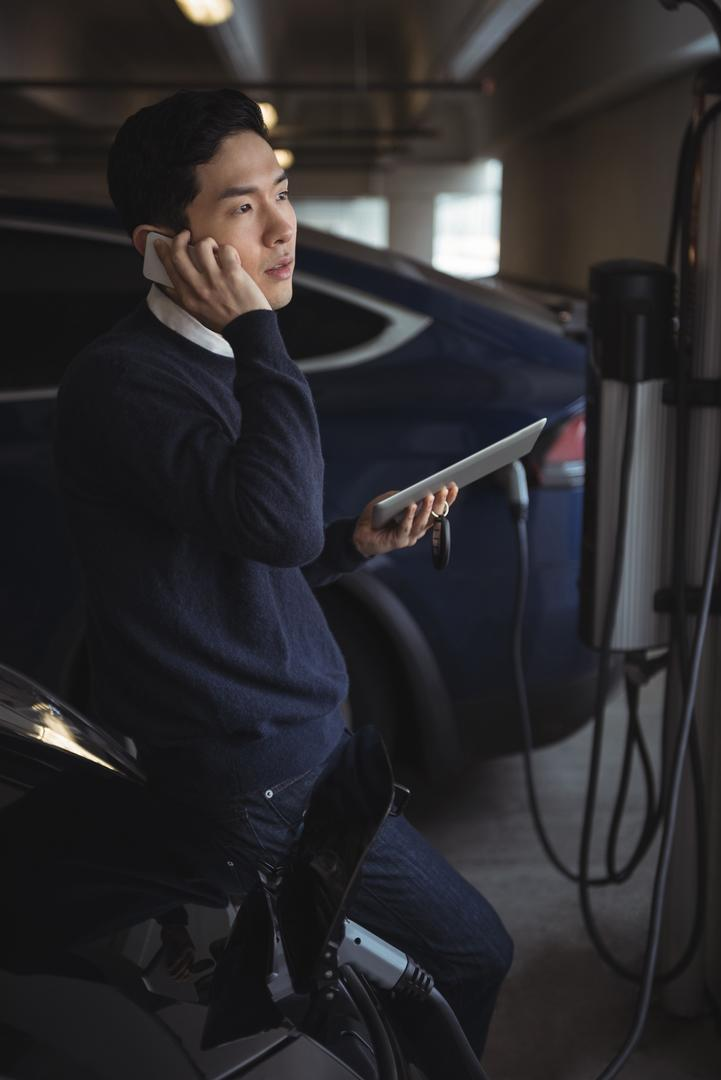 Man talking on mobile phone while charging electric car in garage